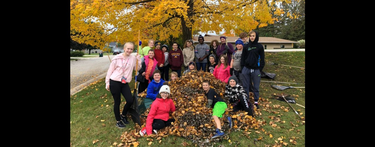 Photograph of students raking leaves